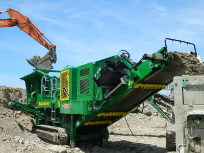 A green McCloskey I44 impact crusher being fed material by an excavator